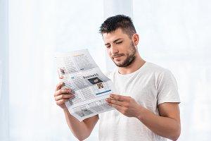 handsome man reading business newspa