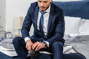 handsome man in suit wearing shoes a