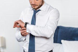 handsome man checking time at wristw