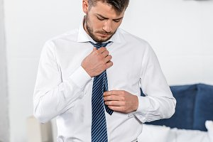 handsome man tying tie in morning in