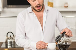 handsome man yawning and pouring cof