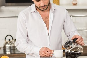 handsome man in shirt pouring coffee