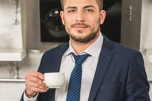 handsome man in suit holding cup of
