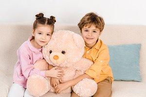 adorable happy kids hugging pink ted