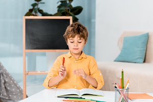 cute kid holding pen and studying at