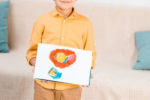 adorable happy boy holding picture a