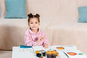 cute happy child painting pictures a