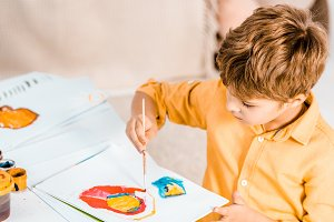 cute little boy painting colorful pi