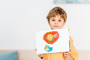 adorable little boy holding picture