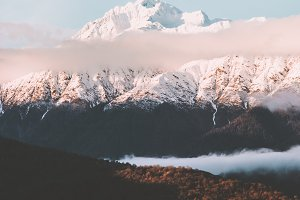 Snowy mountains peak and clouds