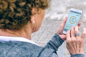 Back view of senior woman using smar