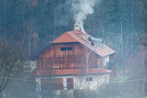 Forest house in the mountains. Smoke