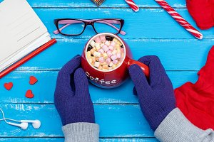 hands in blue mittens hold a red mug