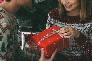 Young woman opens Christmas gift fro