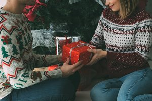 Young woman give Christmas present t