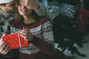 Young man gives Christmas present to