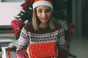 Happy young woman holds Christmas gi