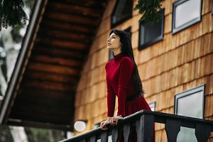woman stand on porch of wooden house