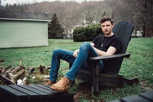 Man sits outdoors on a wooden chair