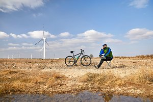 Man with bicycle near wind farm