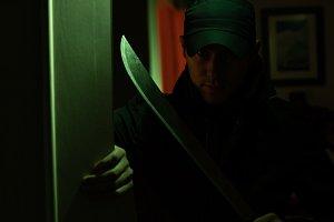 Image of killer with machete in dark