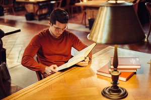 student man in glasses read library