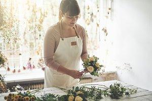 Female florist arranging flowers at