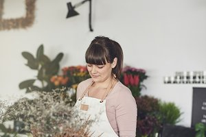 Smiling female florist standing in h