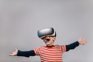 Excited child wearing VR headset.