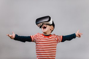 Excited child wearing VR goggles.