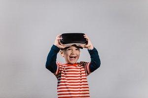 Smiling child wearing VR glasses.