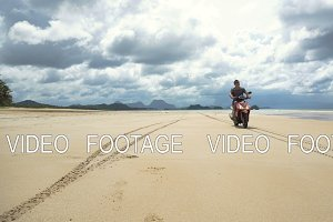 Man driving a motorcycle on beach.