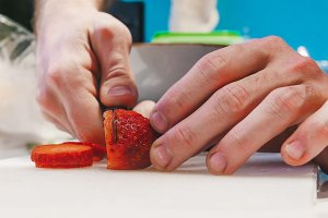 A person cutting strawberries on
