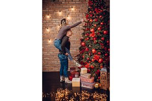 young couple dressing up xmas tree