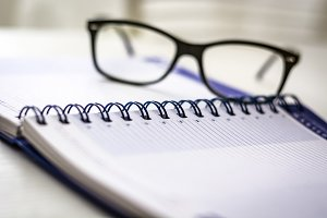 Eyeglasses on a blank spiral diary