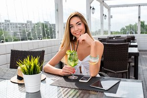 Beautiful woman in summer in a cafe