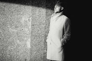 Black and white photo of man in coat