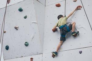 little boy climbing a rock wall