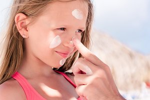 Father applying sun cream to daughte