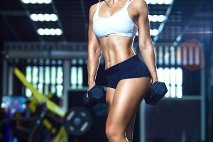 Young fit woman in sporty shorts and