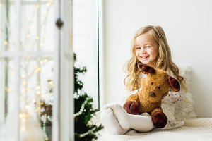 little girl with a plush deer sittin
