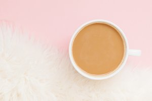 Cup of coffee with milk on pink back