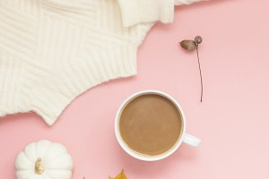 Cup of coffee and white sweater on p