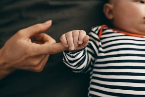 Close up of a baby holding the hand