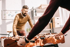 bearded adult man playing table foot