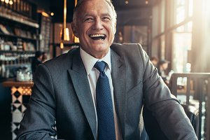 Senior businessman laughing at coffe