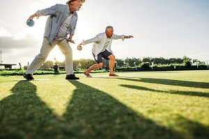 Senior men playing boules in a lawn