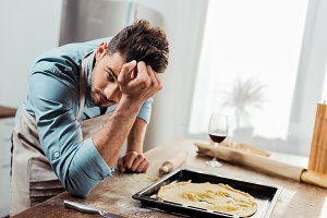 upset young man in apron looking at