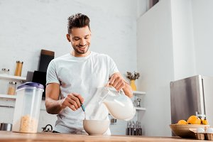 smiling young man pouring milk into