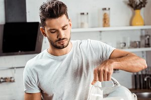 young man pouring milk and cooking o